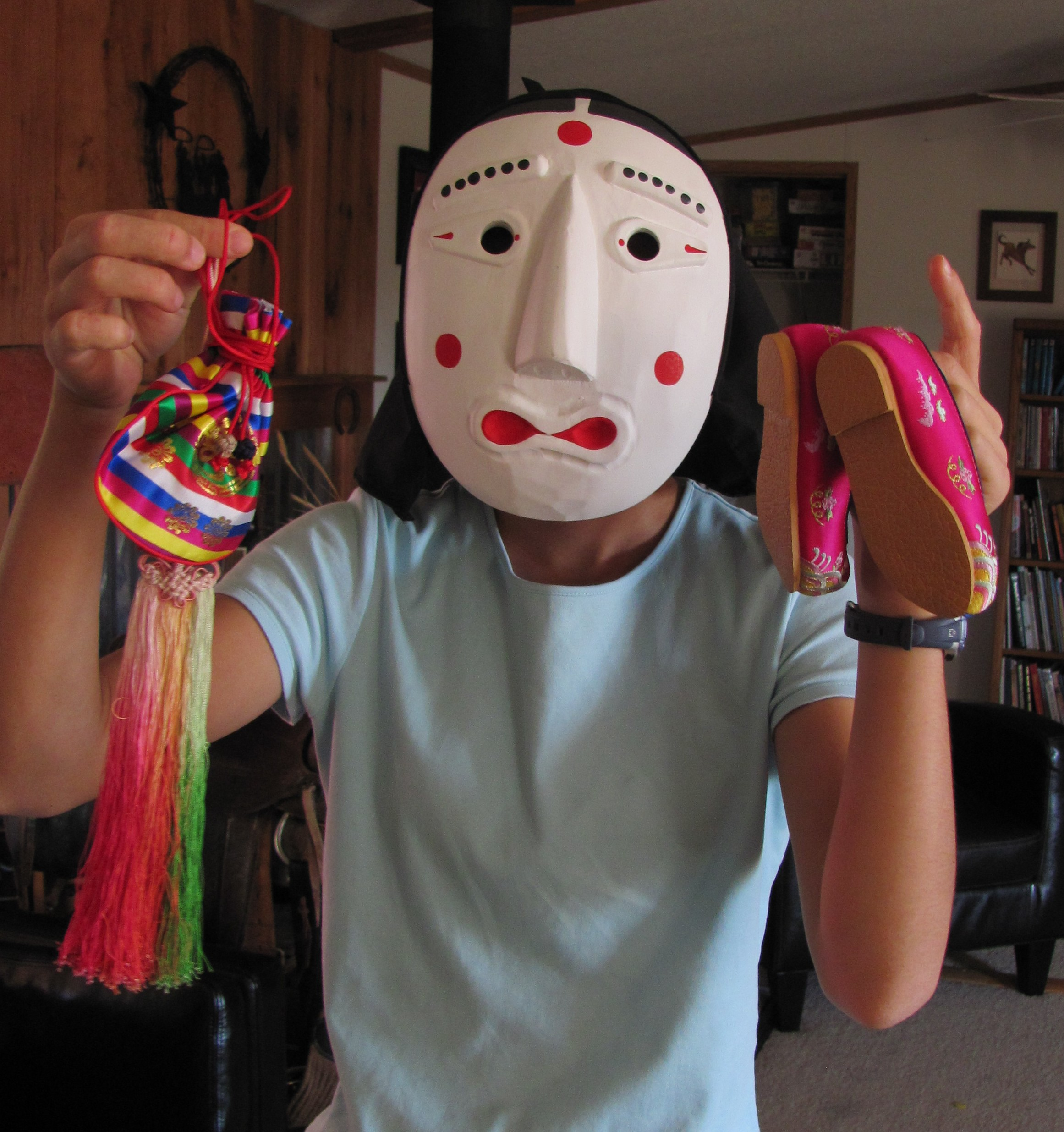 A student poses with objects from the Customs & Traditions Korea Kit